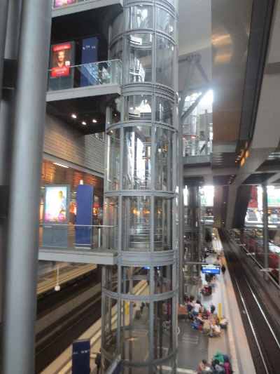 [Berlin]Access to by platforms is by escalators from the mezzanine concourse augmented by these glass lifts providing direct interchange between the two rail levels without needing to use the concourse and access from all floors for the mobility impaired.